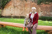 Happy Kid Girl Sitting with Mother on Wooden Tree Trunk Bench by Sandstone Outcrop