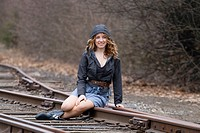 A young woman sitting on train tracks