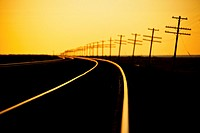 Endless line of telephone poles along rail road tracks at sunrise Imperial Valley, CA