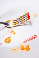 Fork on a plate with crumbs and splatters of ketchuop and egg yolk