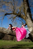 A young woman in a pink dress, laying in a tree