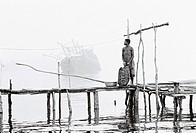 River Niger delta, Bendel State, Nigeria  Woman on wooden jetty at Bennett Island Anchorage on the Warri River shipping channel