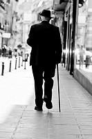 Elderly man elegantly dressed walking down a street, Granada Spain