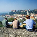 education, school, lessons, drawing lessons in natural surroundings, three schoolboys sitting on a wall at an observation point and paint a picture of...