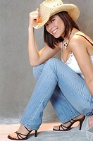 Attractive young woman in straw cowboy hat, tank shirt and jeans