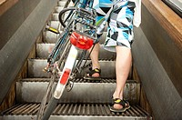 Rotterdam, Netherlands. Legs and feet of a pedestrian biker and bicycle rider, taking the historical wooden escalator in Maastunnel, beneath river Nie...