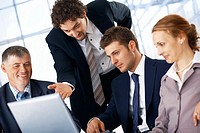 Business man showing something on laptop to his colleagues