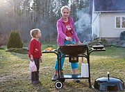 Mother and Kid Girl Standing and Grilling at Barbeque Grill in Yard
