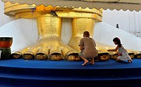 people praying at the feet of the Standing buddha knowns as luang pho at Wat Intharawihan, nakhon district of bangkok, thailand