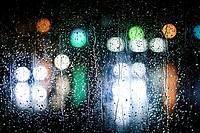 luces desenfocadas en un vidrio lleno de gotas de agua