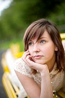 A young slim attractive girl in her late teens or early 20´s thinking, looking pensive thoughtful, UK