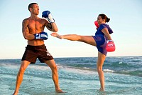 Couple kickboxing on the beach