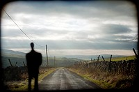 Silhouette of man in front of a country road