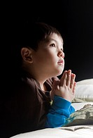 A young boy says his prayers just before his bedtime