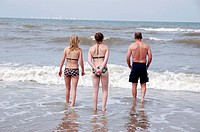 Scheveningen, Netherlands. Three people in swimsuits walking into the salty water of the North Sea for a swim.