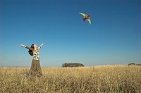 Young woman in field flying kite