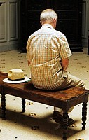 A man sits on a bench in a museum  with his hat by his side