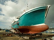 A fishing trawler on the slipway being prepared for a new coat of paint