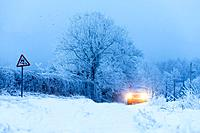A car drives through a winter landscape in Powys, Wales, UK.