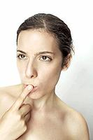 Young woman with finger over her mouth