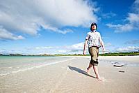 Person walks along scenic white sand beach, Gimsøya, Lofoten islands, Norway