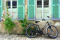 Bicycle in front of a House surrounded by flowers and Hollyhock Alcea Rosa, Saint Martin en Re, Ile de Re, Charentes Maritime department, France, Euro...