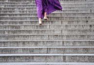Young woman walking up staircase outdoors rear view