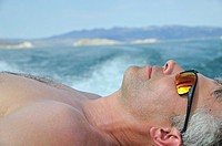 Man sunning on deck of boat, Lake Mead, Nevada, USA