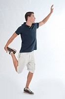 Full-body photograph of a teenage boy standing with a jump or making a pirouette.