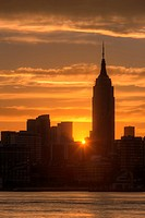 The rising sun shines between Manhattan buildings including the Empire State Building just after sunrise, New York City, New York, USA
