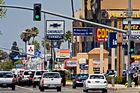 Afternoon traffic passes retail advertising signs in Costa Mesa, CA  Note haze from summer heat