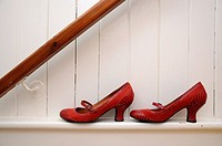 Red shoes on white wall