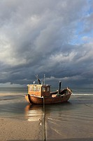 traditional wooden Fishing boat on the beach in the seaside resort of Ahlbeck in sunlight before thundershower, Usedom, Mecklenburg-Vorpommern, German...