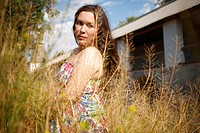 brunette women 25-30 years staying in the yellow grass against old gallery building