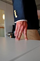 Man in jacket rests fingers on table (Notice: Four button, four fingers), Stockholm, Sweden
