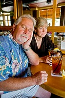 A middle aged couple appeared indifferent to each others´ company over iced tea together in a Long Beach, CA, restaurant