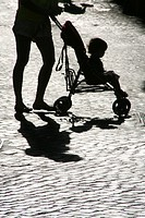 mother pushing pram buggy in street