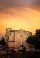 After a rainstorm a rainbow appears over the 13th century Church of St. Saturnin on the outskirts of Pezenas, France