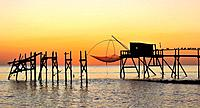 Traditional carrelet fishing hut with lift net on the beach at sunset, Loire_Atlantique, France