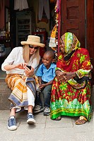 Tourist showing photos on her smart phone to local woman and child in East African market.