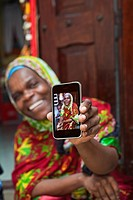 Local woman in East African market and holding smart phone with her photo.