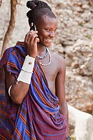 Maasai man wearing traditional dress and using modern smart phone.