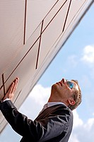 Brown haired young man with sunglasses, looking up into the air, supporting himself by with one hand at the wall, blue skyl, Hamburg, Germany, Europe
