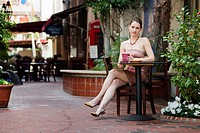 A young Caucasian woman sitting alone drinking an espresso