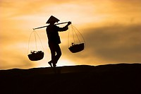 Woman with conical hat carries pannier baskets in sunrise along crest of sand dunes near Mui Ne Vietnam
