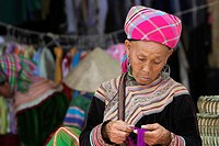 Old woman sorts coloured yarn Bac Ha hilltribe market known for colourful Flower Hmong traders north Vietnam