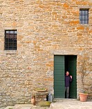 Woman waving from a doorway in Tuscany, Italy