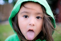 A little girl with her tongue sticking out looking sick.
