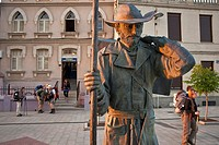 Morning sunlight on pilgrim statue as pilgrims depart for a days walk in the city of Astorga along the Camino de Santiago