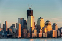 The sunset colored sky is reflected off of the building facades in lower Manhattan, including the World Financial Center and Battery Park City. The ri...